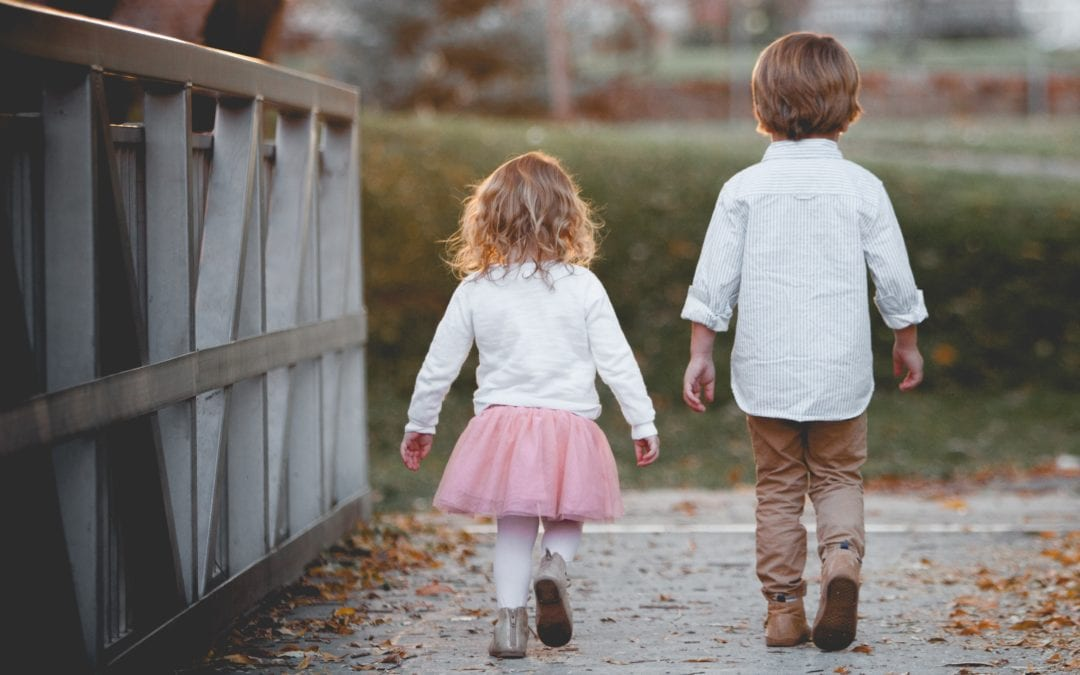 Two small children walking over a bridge